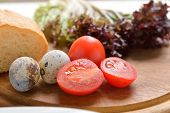 stock photo of quail egg  - quail eggs bread tomatoes and lettuce on a wooden cutting board - JPG