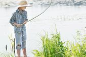 stock photo of chums  - Angling teenage boy is looking at handmade green twig fishing rod in his arms - JPG
