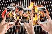 stock photo of grilled sausage  - friends using smartphones to take photos of sausage and pork chop and vegetables on the flaming grill - JPG