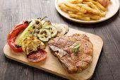 foto of pork chop  - Fried pork chop chips and vegetable on wooden background - JPG