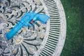 stock photo of pistols  - A blue water pistol lying on an old table in a garden - JPG