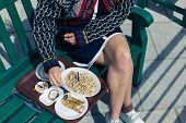 stock photo of smoking woman  - A young woman is eating cokcles and smoked fish outside on a sunny day - JPG