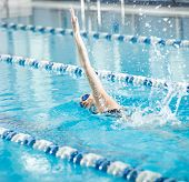 stock photo of goggles  - Young woman in goggles and cap swimming front crawl stroke style in the blue water indoor race pool - JPG