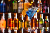picture of liquor bottle  - Martini drink served on bar counter with blur bottles on background - JPG