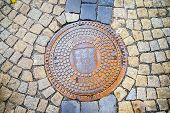 stock photo of sewage  - Hatch of sewage on the paving road in Tabor Czech Republic - JPG