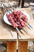 pic of kebab  - raw lamb shish kebabs on skewers in outdoor cafe - JPG