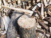 stock photo of ax  - wood chopper ax in block for chopping firewood pile of wood on rustic courtyard - JPG