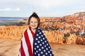 stock photo of bundle  - Cute laughing boy who is bundled up into American flag - JPG