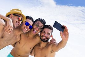 foto of selfie  - Group of four male friend taking a selfie at the beach - JPG