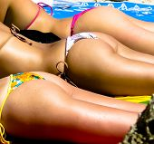 stock photo of tanga  - Three close up girls butties on a beach - JPG