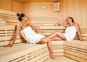 image of sauna  - Beautiful young females relaxing in wooden spa room eyes closed - JPG