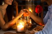 Romantic couple holding hands together over candlelight during romantic dinner  poster