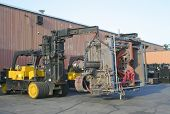 image of boom-truck  - a pair of fork trucks moving a big press  - JPG