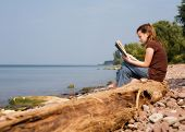 image of girl reading book  - Middle school girl reading a book on a rocky beach - JPG