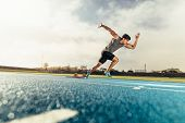 Sprinter Taking Off From Starting Block On Running Track poster
