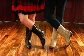 stock photo of lady boots  - Female Legs in Cowboy Boots in a Line Dance Step on hardwood floor - JPG