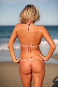 foto of string bikini  - sexy bronzed woman in brief bikini on the beach with back turned - JPG