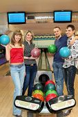 Four students stand near tenpin bowling with balls for playing bowling and smile, focus on girl in c
