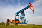 stock photo of nonrenewable  - Oil pump jack on empty field - JPG