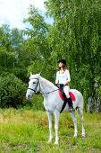 foto of appaloosa  - Image of happy female jockey sitting on appaloosa horse outdoors - JPG