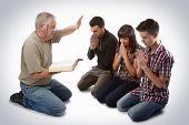 stock photo of preacher  - Preacher leading three young souls in prayer to receive Jesus - JPG