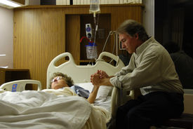 stock photo of hospital patient  - Holding the hand of a sick loved one in the hospital and praying.  - JPG