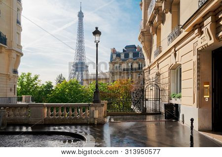 poster of Cosy Paris Street With View On The Famous Eiffel Tower On A Cloudy Summer Day, Paris France