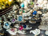 Defocused View Of Jewelry Store With Multiple Rings And Earrings With Blue Magenta Precious And Semi poster