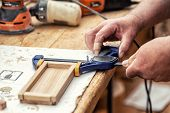 Close-up Senior Carpenter Glueing Wooden Craft Surface And Joining With Clamps. Woodwork Carpenter W poster