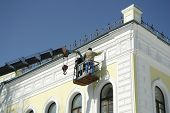 picture of scaffold  - Man on the elevating platform painting a building facade - JPG