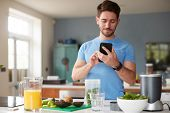 Man Using Fitness Tracker To Count Calories For Post Workout Juice Drink He Is Making poster