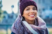 Closeup face of a young happy african woman enjoying winter wearing scarf and cap. Smiling brazilian poster