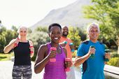 Group of mature happy people using dumbbells for workout session. Multiethnic group of smiling women poster
