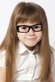 A Portrait Of The Smiling Girl Wearing Glasses