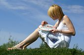 Woman Cross-Stitching In The Park With Blue Sky On Background