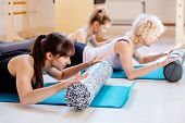 Female Instructor Workout With Foam Rollers, Blue Mats Performing Physical Pilates Exercises Lying O poster