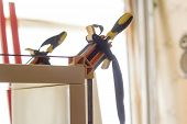 Gluing And Fixing Wooden Furniture With A Few Clamps On A Blurred Background Of A Carpentry Workshop poster