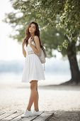 Young Beautiful Woman In A White Dress Standing With A Backpack On The Beach. Beautiful Sensual Mixe poster