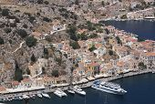 Greece, The Island Of Symi. A View From The Top Of The Bay Down To The Harbor. Pleasure Craft Docked poster