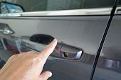A Woman Using Her Finger To Lock A Car Door Keylessly. Keyless Entry Car Key.  A Keyless Entry Syste poster