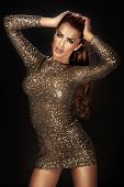 foto of cleavage  - Photo of beautiful woman dancing in gold shining dress over the black background - JPG