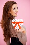 image of tease  - Vivacious beautiful brunette woman with a heart shaped Valentine gift looking seductively back at the camera over her shoulder - JPG