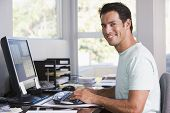 Man In Home Office Using Computer And Smiling