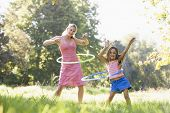 stock photo of hulahoop  - Portrait of woman with children smiling in park - JPG