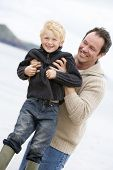 image of portrait middle-aged man  - Portrait of man and son on beach in wintertime - JPG