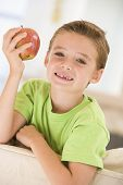 Young Boy Eating Apple In Living Room Smiling