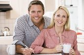 stock photo of current affairs  - Couples in a kitchen looking at eachother with a newspaper infront of them - JPG