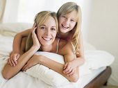 image of young girls  - Families laid in bed at home smiling - JPG