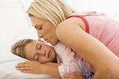 stock photo of goodnight  - Woman tucking child into bed - JPG