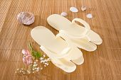 stock photo of spanking  - Spa or hotel flip flops on a bamboo mat - JPG
